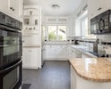 Well-equipped eat-in chef's kitchen with double oven and granite countertops