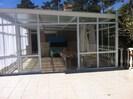 Terrasse complètement couverte en vitres donnant sur 1 autre terasse et cuisine