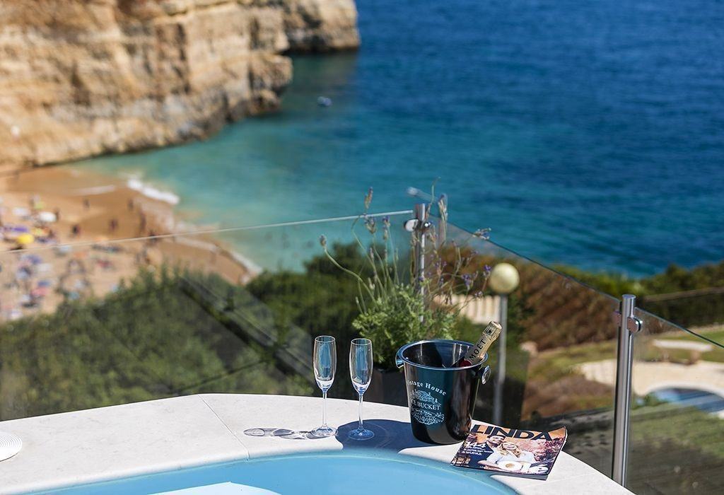 Champagne bottle and glasses at the side of a pool overlooking a bay in Portugal