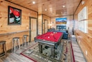 Lower game room with pool table, large screen TV, and sleeper sofa.