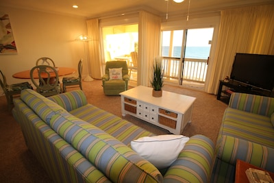 Spacious living area with oceanfront views and balcony access