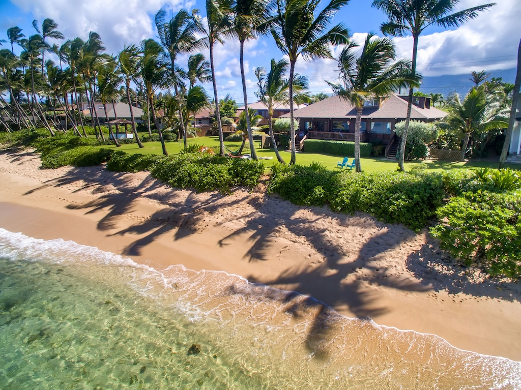 Wavind palms and a beachfront home along the North Shore of Oahi