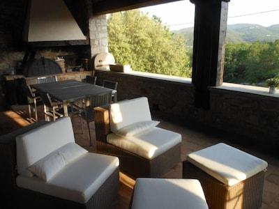 """Grande terrasse couverte plein sud (""""couradou"""") avec barbecue et four à pizza"""