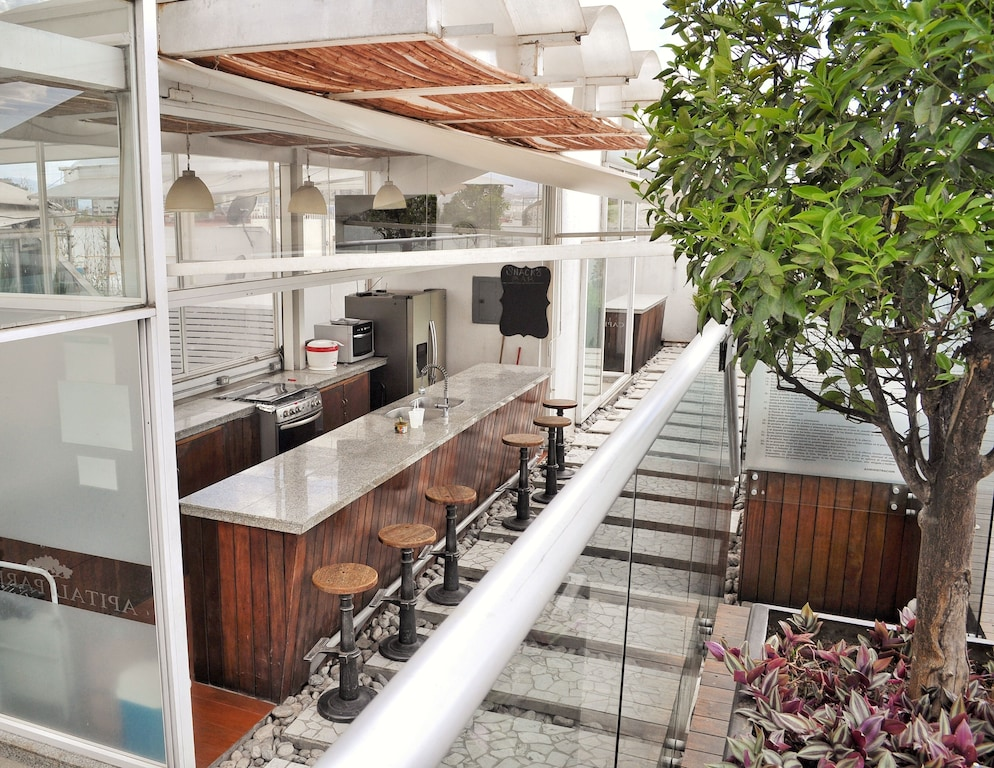 VRBO Mexico City: Rooftop restaurant outdoors at a with bar seating and a kitchen