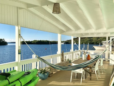 Spacious ocean front balcony with 2 hammocks, dinning table for 10 and seating.