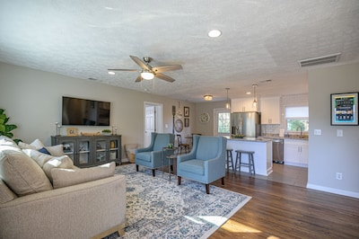 Professionally decorated living room with mounted smart TV, open floor plan with access to the kitchen and dinning room.