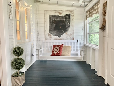 air conditioned front porch with swing and breakfast table
