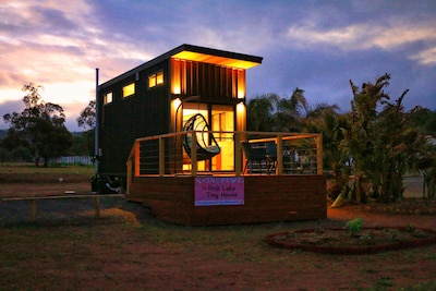 Pink Lake Tiny House with outdoor deck at dusk