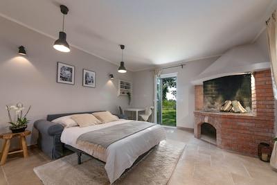 Wohnraum/Schlafraum mit Kamin und Eingang vom Garten