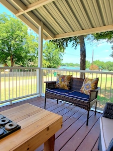 Large covered front porch with a view of the lake across the street.