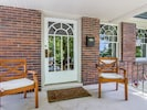 Charming covered front porch with 2 chairs