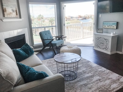 open living room layout with French Doors that look straight out to a water view