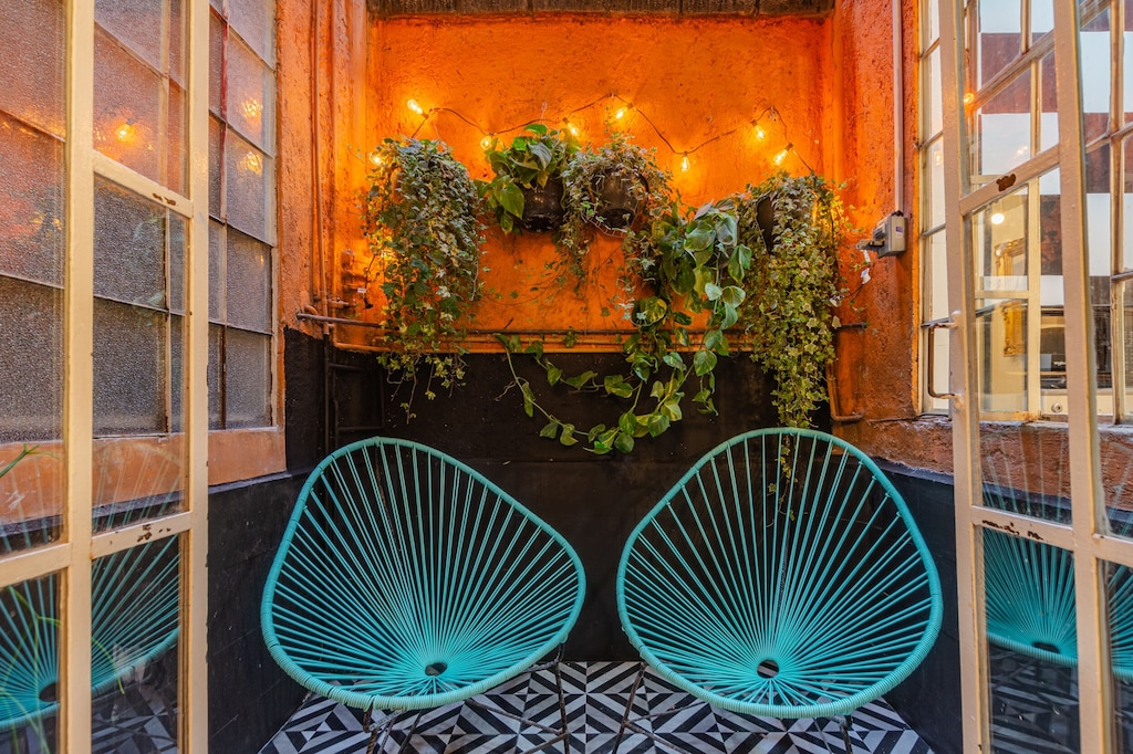 VRBO Mexico City: Small outdoor garden with plants on the wall & two blue chairs