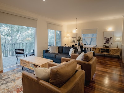 Living/dining area with fold out sofa and floor to ceiling windows