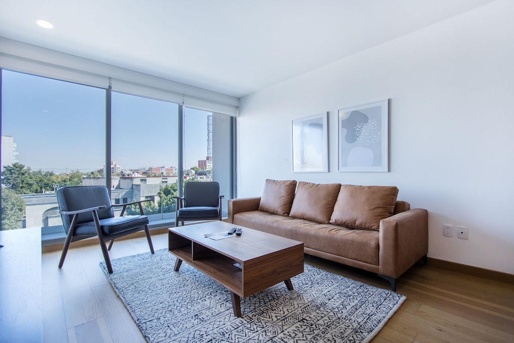 VRBO Mexico City: Apartment with a sofa, two chairs, coffee table and large windows overlooking the city