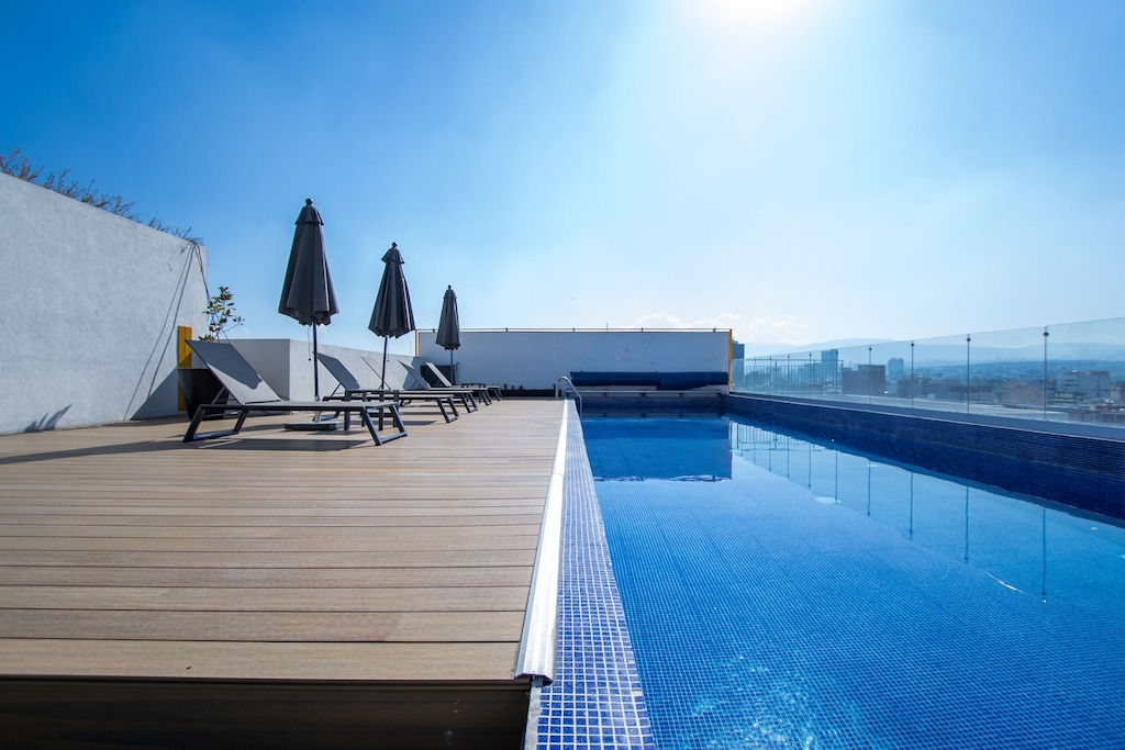 VRBO Mexico City: Rooftop pool and lounge deck with chairs and umbrellas overlooking the city