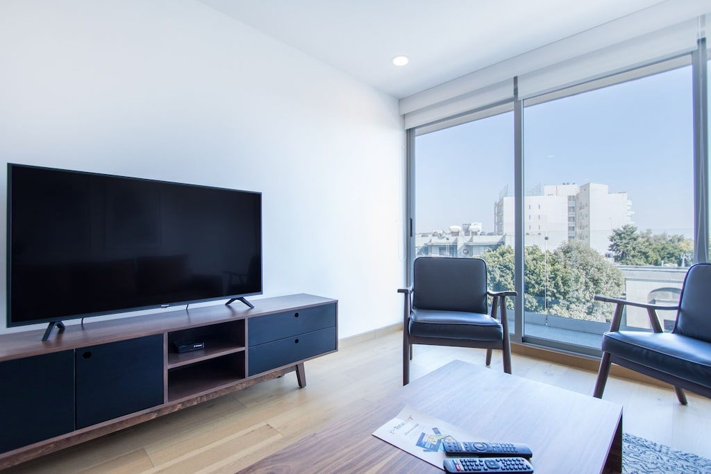 VRBO Mexico City: Apartment with a large TV, two chairs and large windows overlooking the city
