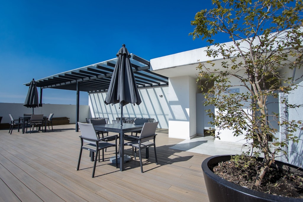 VRBO Mexico City: Rooftop lounge area with seating, table and umbrella