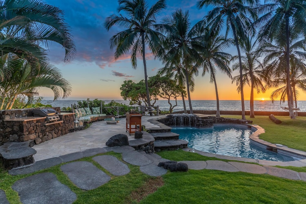 Image of a gorgeous Hawaiian sunset view of the pool area at this stunning villa in Hawaii.