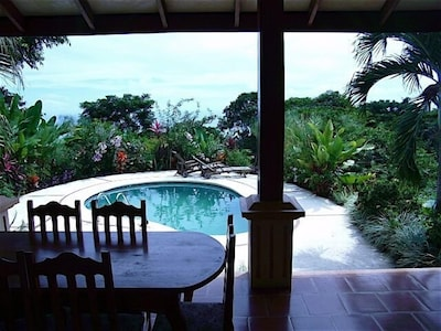 View of pool from veranda with ocean in background