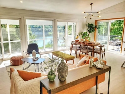 """Ours guests say its, """"LOVE AT FIRST SIGHT""""! As you enter the house, you are greeted with an expansive view of the Iowa river! Take a moment to sit on the beautifully appointed mid-century modern furniture and take in the views!"""