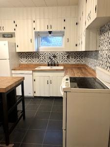 New tile floors, backsplash, kitchen island, fixtures & freshly painted cabinets