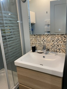 Salle de bain avec meuble vasque et mitigeur thermostatique.