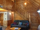 Living room with comfortable reclining sofa, & stairs leading to upstairs Loft