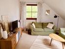 Das Wohnzimmer ausgestattet mit zwei Sofas und einem Fernseher