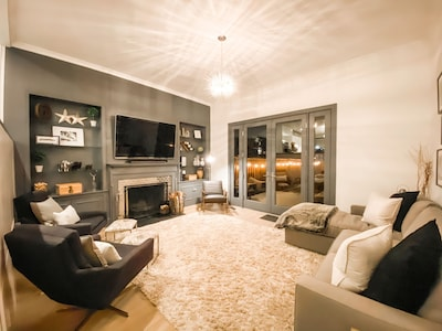 Main living room has high ceilings, a starburst chandelier, and backyard access.