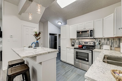 Kitchen w full sized range, refrigerator, coffee maker and counter seating