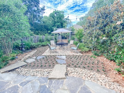 Patio with professionally maintained landscape and beautiful, antique fountain.
