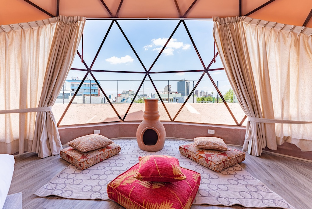 VRBO Mexico City: Peach colored geodesic dome apartment rental with bed and seating area