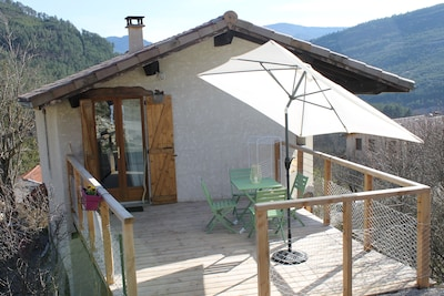 Terrasse spacieuse en bois avec salon de jardin, parasol et 2 chaises longues