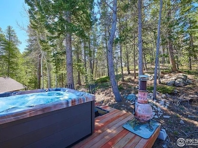 A hot tub surrounded by forest.
