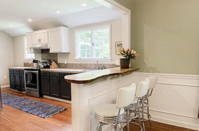 Large kitchen with custom raw edge wood breakfast bar
