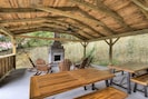 Outdoor covered patio with fireplace, picnic tables, grill and ping pong table