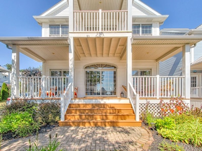 Large, waterfront home with balcony and patio at the front