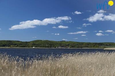 Einen Steinwurf von der Ferienwohnung entfernt tut sich der Blick über den Neuensiener See zum Jagdschloss Granitz auf.